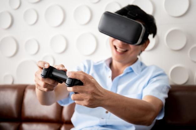 Homem adulto asiático jogando videogame usando óculos de realidade virtual na sala de estar Foto Premium