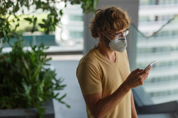 Homem adulto barbudo branco usando smartphone enquanto usava máscara cirúrgica em uma parede industrial. saúde, epidemias, redes sociais. Foto gratuita