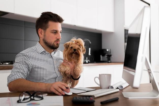Homem adulto bonito segurando animal de estimação enquanto trabalha Foto gratuita