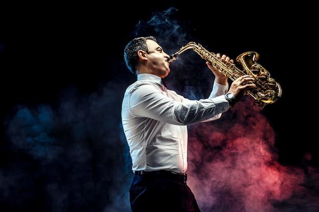 Homem adulto bonito tocando saxofone Foto Premium