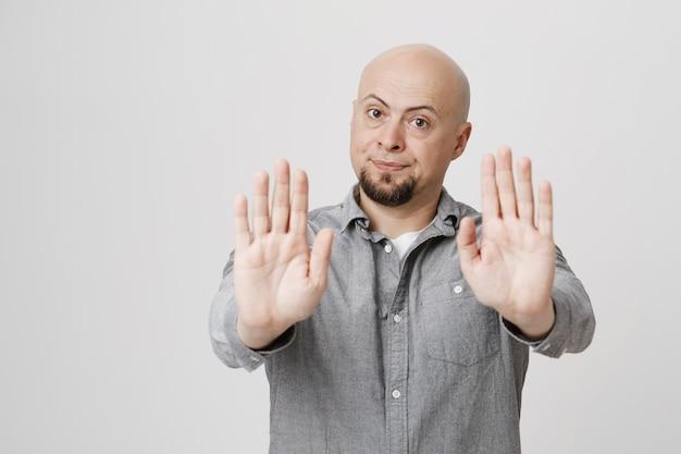 Homem adulto careca insatisfeito mostra sinal de parada, ação proibida Foto gratuita