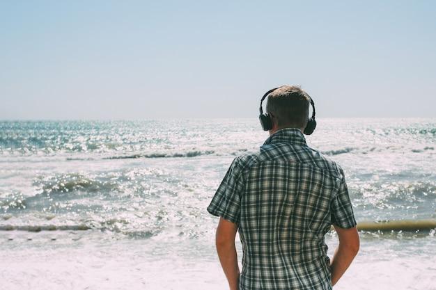 Homem adulto com fones de ouvido, olhando para o mar tempestuoso Foto Premium