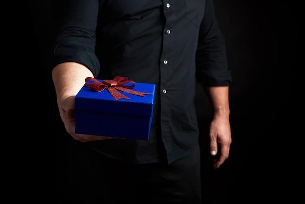 Homem adulto em uma camisa preta segura uma caixa quadrada azul com um laço vermelho amarrado em um fundo escuro Foto Premium