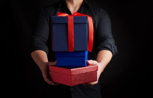 Homem adulto em uma camisa preta tem em suas mãos uma pilha de presentes embrulhados em papel Foto Premium