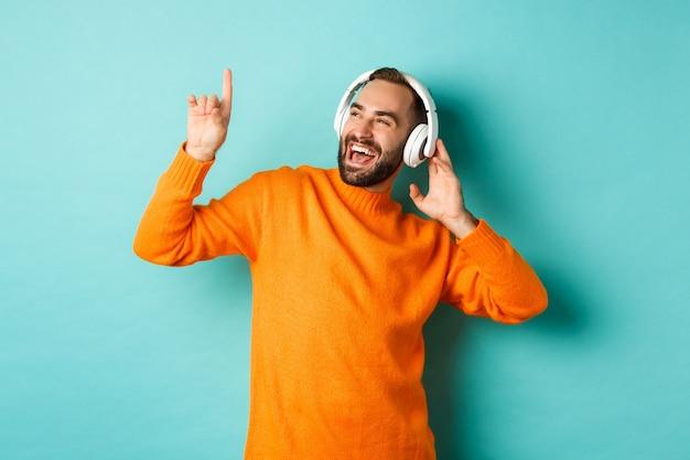 Homem adulto feliz com suéter laranja, olhando para cima e ouvindo música no fone de ouvido, encostado na parede turquesa Foto gratuita