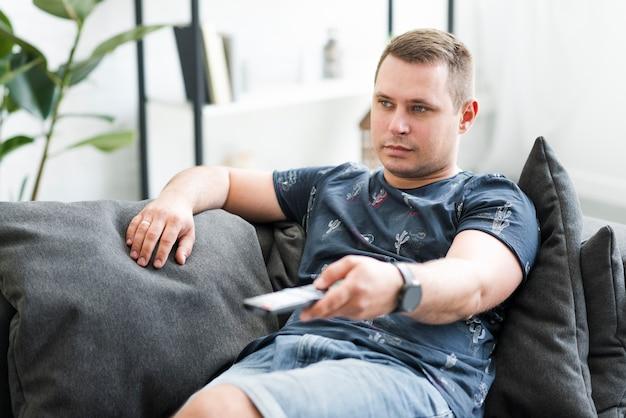 Homem adulto meio, sentando, ligado, sofá, olhando tv Foto gratuita