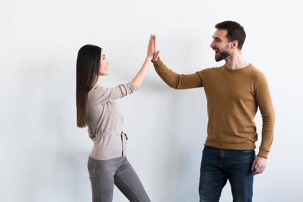 Homem adulto positivo e mulher jovem de fiving Foto gratuita