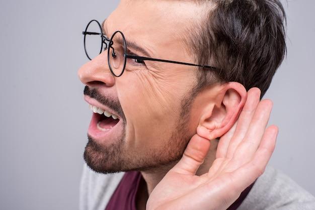 Homem adulto que escuta secretamente na conversação confidencial. Foto Premium