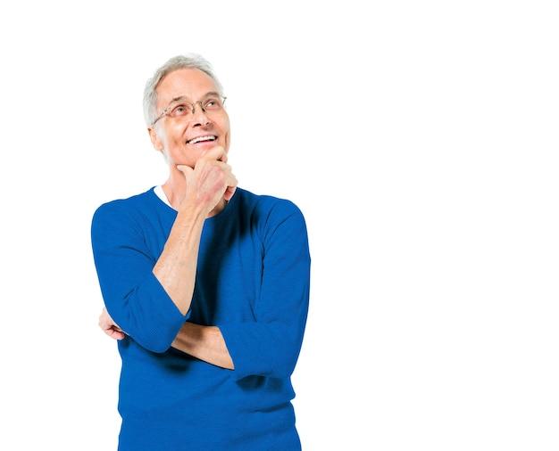 Homem adulto sênior em pé com a mão no queixo sorrindo e comtemplating Foto gratuita