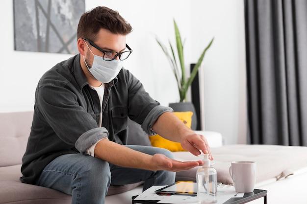 Homem adulto usando desinfetante para as mãos em casa Foto Premium