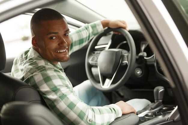 Homem africano alegre sorrindo para a câmera, sentado em seu carro novo na concessionária. Foto Premium