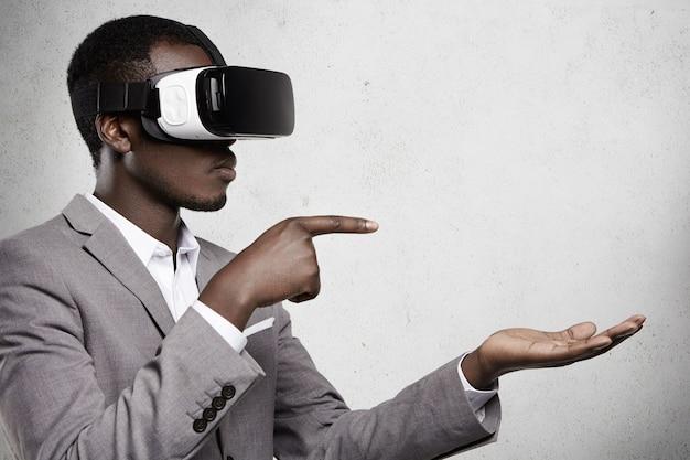 Homem africano atraente com roupa formal e óculos 3d, apontando os dedos para o espaço da cópia acima da palma da mão aberta, como se estivesse usando algum gadget. Foto gratuita