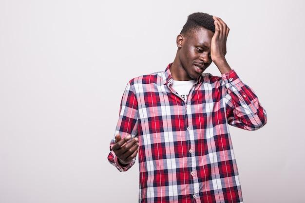 Homem africano chateado e triste agarrando sua testa com a mão em pé, perdendo o prazo de inscrição da loteria de diversidade ou esquecendo de desligar a eletricidade em casa. Foto gratuita