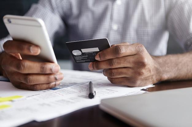 Homem africano com camisa pagando mercadorias na internet usando cartão de crédito e telefone celular Foto gratuita