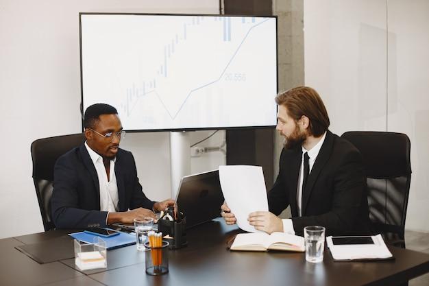 Homem africano de terno preto. parceiros internacionais. Foto gratuita