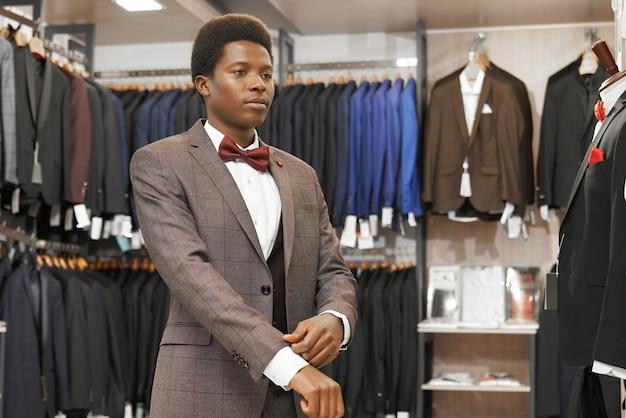 Homem africano escolhendo terno elegante na moda boutique. Foto gratuita