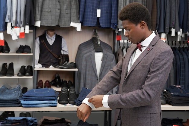 Homem africano experimentando terno na boutique, olhando para a manga. Foto gratuita