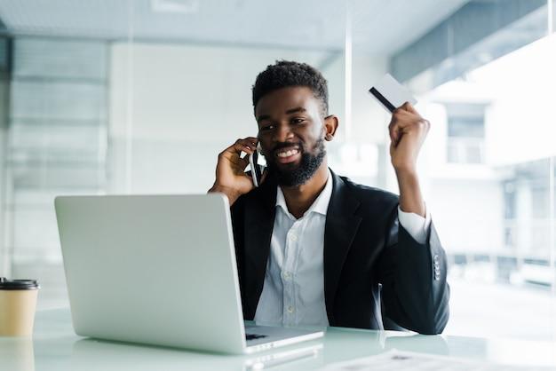 Homem africano falando no telefone e lendo o número do cartão de crédito enquanto está sentado no escritório Foto gratuita