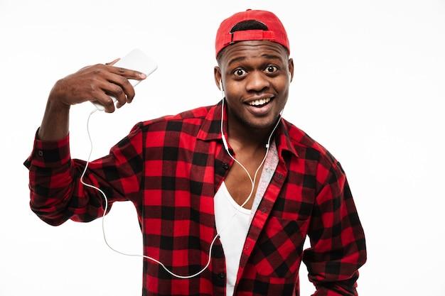 Homem africano feliz espantado, ouvindo música do telefone celular Foto gratuita