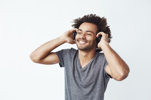 Homem africano feliz sorrindo ouvindo música em fones de ouvido. Foto gratuita