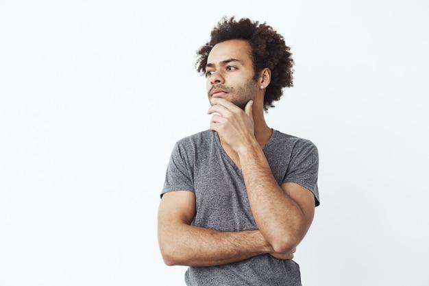 Homem africano incerto pensando olhando de lado por cima da parede branca, decidindo se compra alguns gadgets on-line ou um estudante tentando se lembrar de uma festa. Foto gratuita