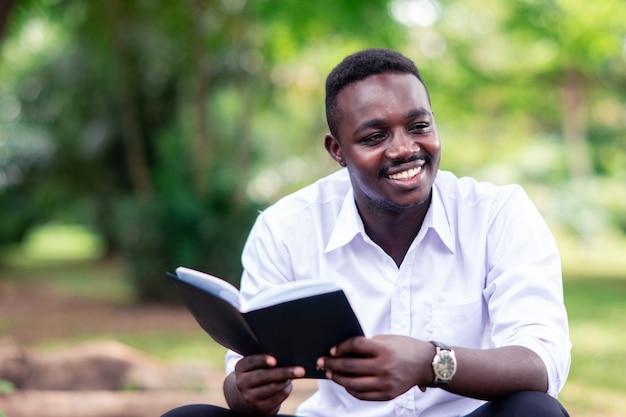 Homem africano, lendo um livro, parque Foto Premium