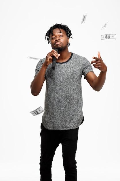 Homem africano novo que canta no microfone no branco. Foto gratuita