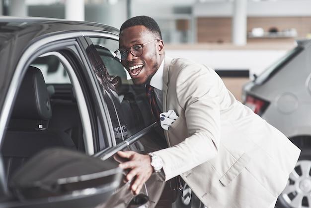 Homem africano olhando para um carro novo na concessionária. Foto gratuita
