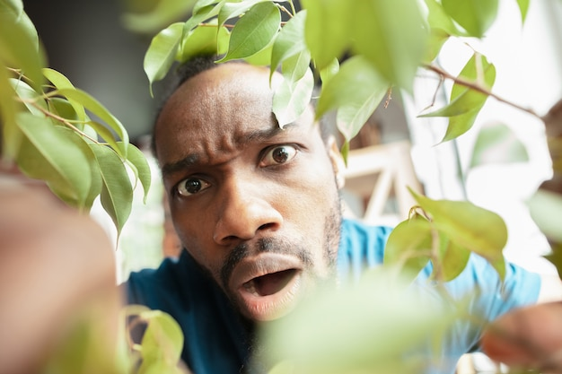 Homem afro-americano à procura de algo em lugares incomuns em sua casa Foto gratuita