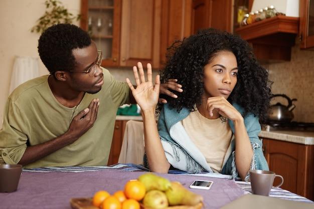Homem afro-americano apologético, segurando a mão no peito, tentando convencer a mulher louca em sua fidelidade. mulher negra, ignorando as desculpas de seu marido infiel. problemas de amor e relacionamentos Foto gratuita