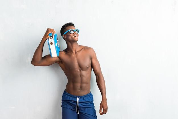 Homem afro-americano, aproveitando as férias de verão, segurando o rádio vintage e olhando para cima Foto Premium