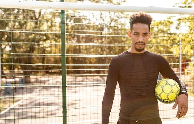Homem afro-americano brincando com uma bola de futebol em um campo Foto gratuita