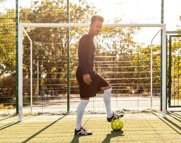 Homem afro-americano brincando com uma bola de futebol lá fora Foto gratuita