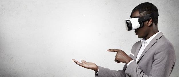 Homem afro-americano com roupa formal, usando fone de ouvido de realidade virtual 3d para telefone inteligente. Foto gratuita