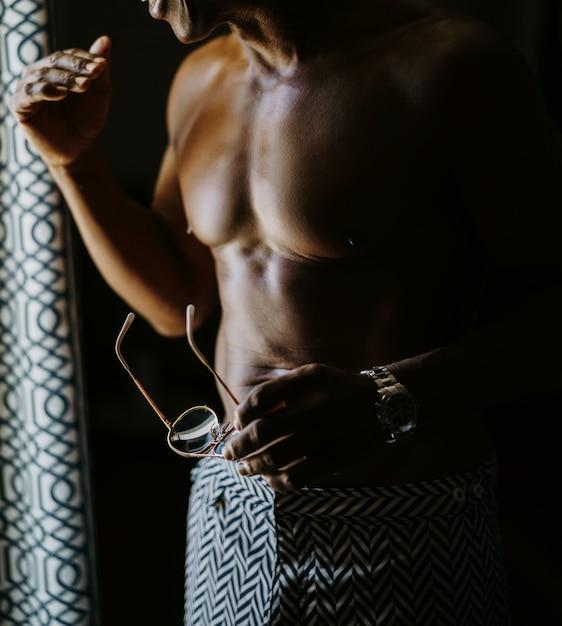 Homem afro-americano com torso nu se prepara em pé antes Foto gratuita