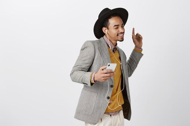 Homem afro-americano dançando despreocupado, ouvindo música em fones de ouvido, sorrindo e segurando um smartphone Foto gratuita