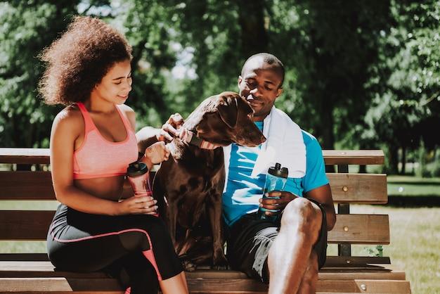 Homem afro-americano e linda garota no banco do parque Foto Premium