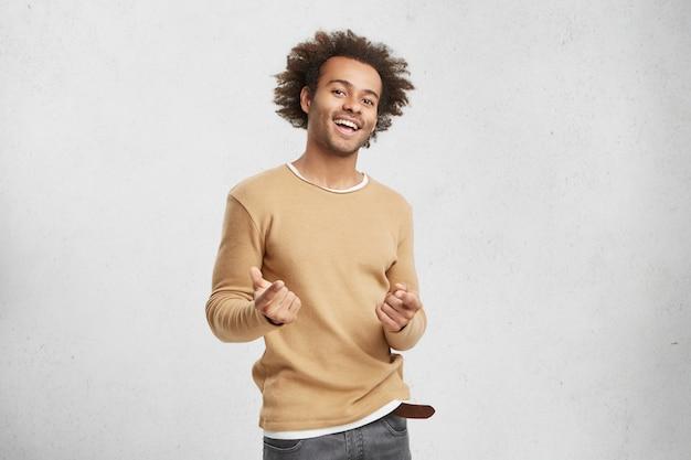 Homem afro-americano elegante e feliz, usando roupas casuais, apontando para a câmera com os dedos da frente Foto gratuita