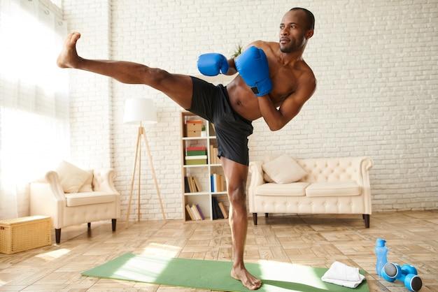 Homem afro-americano em luvas de boxe faz chute. Foto Premium
