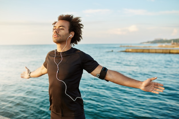 Homem afro-americano esportivo, esticando os braços antes do treino ao ar livre. atleta magro e forte de camiseta preta, de braços abertos, respirando o ar fresco do mar. Foto gratuita