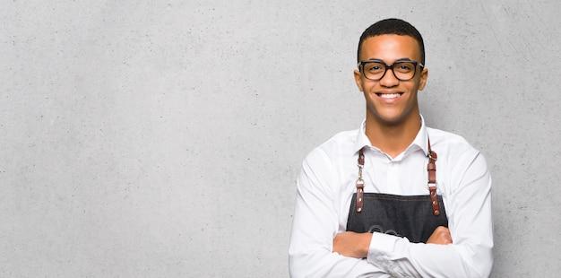 Homem afro-americano jovem barbeiro com óculos e feliz na parede texturizada Foto Premium