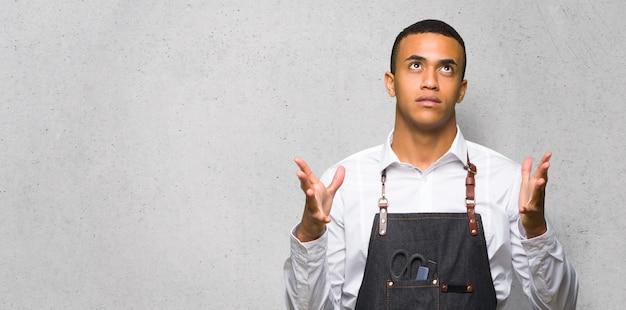 Homem afro-americano jovem barbeiro frustrado por uma situação ruim na parede texturizada Foto Premium
