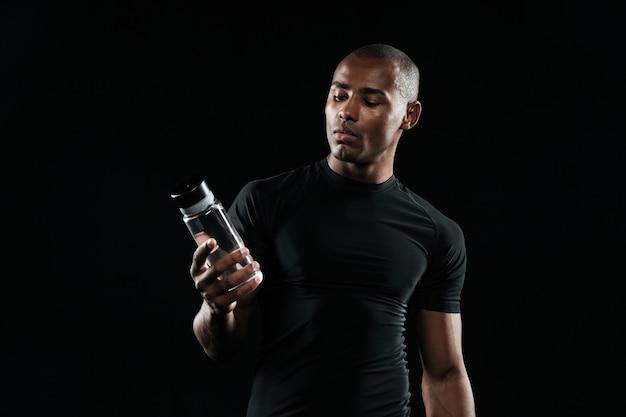 Homem afro-americano jovem esportes segurando a garrafa de água Foto gratuita