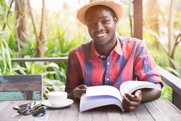 Homem afro-americano lendo um livro com café, chave e smartphone. Foto Premium
