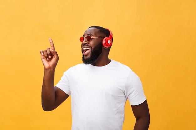 Homem afro-americano novo considerável que escuta e que sorri com música em seu dispositivo móvel. isolado sobre o fundo amarelo. Foto Premium