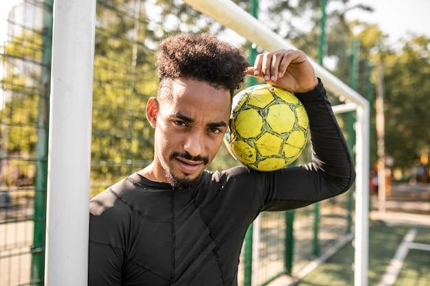 Homem afro-americano posando com uma bola de futebol em um campo Foto gratuita