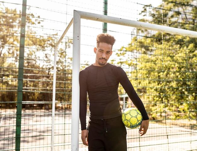 Homem afro-americano posando com uma bola de futebol Foto gratuita