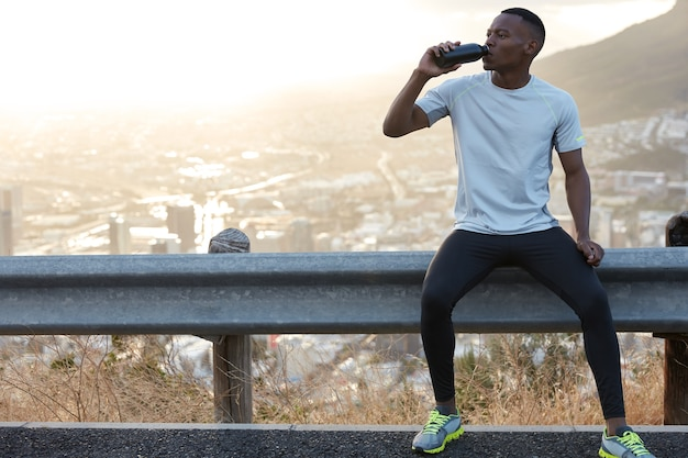 Homem afro-americano sedento bebe água doce, aproveita o intervalo após os treinamentos esportivos ao ar livre, senta-se em uma placa de estrada com uma cópia da vista panorâmica da montanha para conteúdo promocional ou informações Foto gratuita