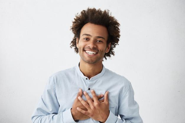 Homem afro-americano simpático e simpático, de camisa branca, sorriso encantador e expressão amigável Foto gratuita