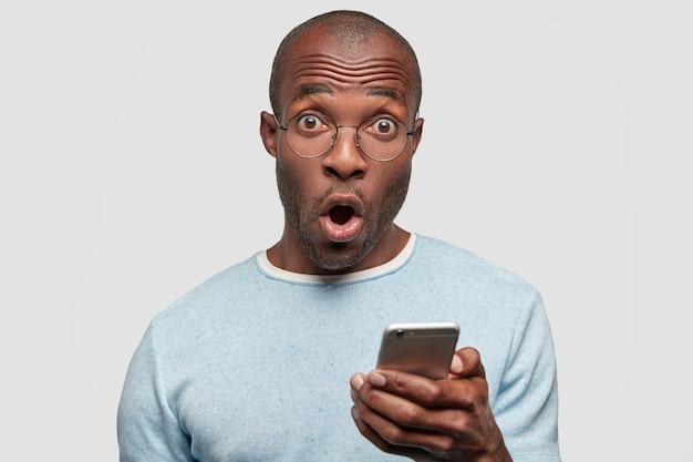 Homem afro-americano surpreso olhando desesperadamente para a câmera Foto gratuita